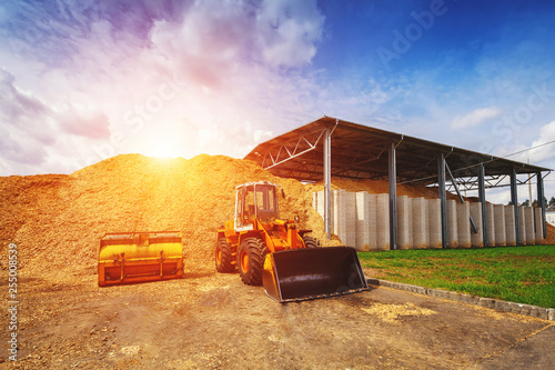 Obraz na plátne  single-bucket front heavy loader standing on the background of a large pile of chips for heating boilers