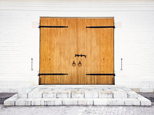 White Brick Wall With Wooden Door Bolt, Handles And Hinges Made Of Wrought Iron. Medieval Architecture