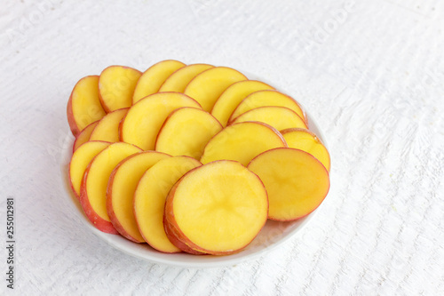 Fotografie, Obraz  sliced potatoes solanum tuberosum with peel in a white bowl side view on a woo