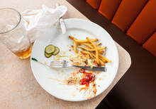 Remains Of A Satisfying Meal On Empty Plate. Dirty Dishes In Restaurant Cafe Diner.