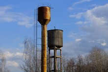 Two Old Water Towers Of Metal And Wooden Against The Sky