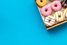 Glazed Decorated Donuts In Box On Blue Background Flat Lay Mock Up