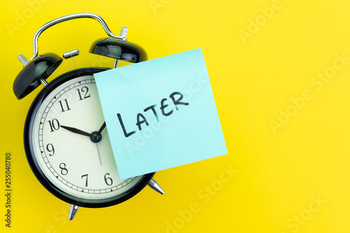 Fotografía Sticky post with handwriting the word Later stick on alarm clock on solid yellow