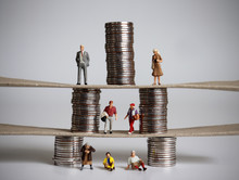 The Concept Of Pyramid Of Social Class. Miniature People And Piles Of Coins.