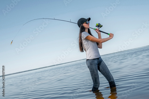 Poster Peche Fishing concept. Young fisherwoman makes a cast on background of skewed horizon line