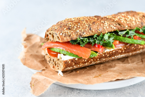 Foto op Canvas Snack sandwich from a cereal baguette with avocado, salmon, cream cheese, tomatoes and lettuce leaves on a white plate. light background, selective focus and copy space.