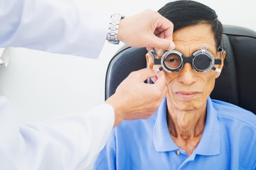 Elderly man having hes eyes examined by an eye doctor on a testing tool in modern clinic, optometry concept