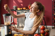 Young woman making healthy smoothie at home