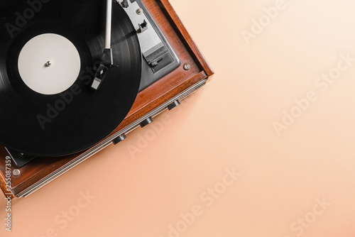 Photo  Record player with vinyl disc on color background