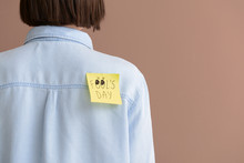 Sticky Note With Text FOOL'S DAY On Back Of Young Woman Against Color Background