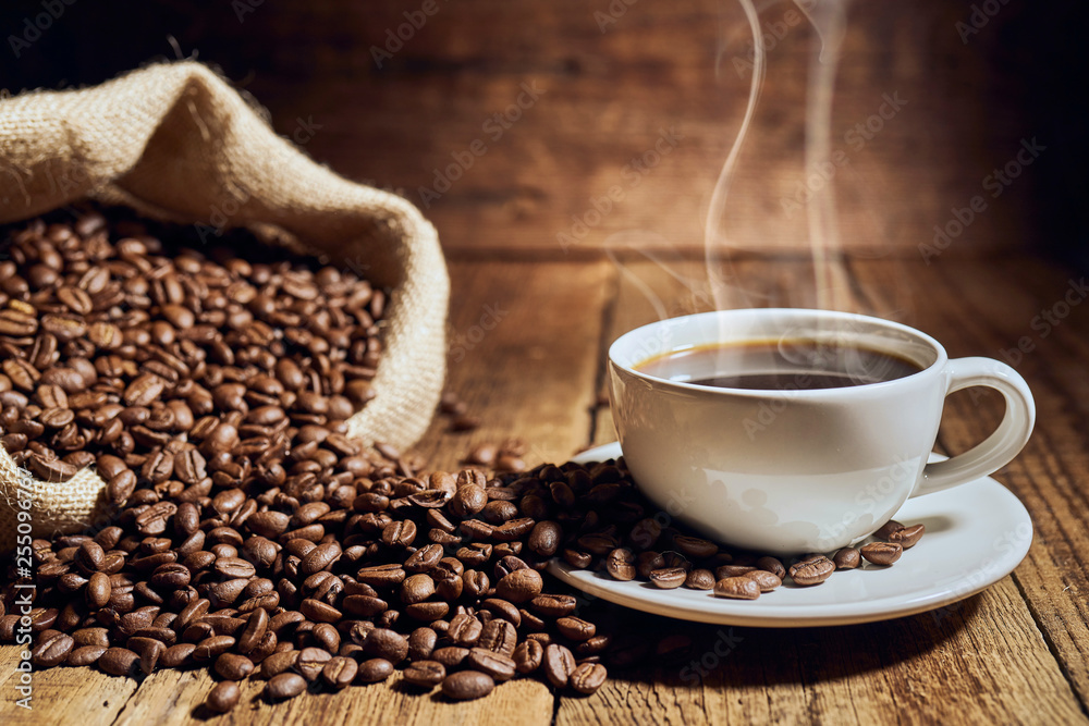 Fototapeta Czarna kawa na starych deskach i rozsypane ziarna