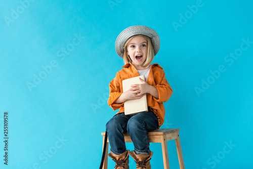 Fotografija  surprised kid in jeans and orange shirt sitting on stairs and holding book isola