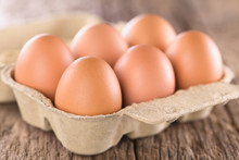 Raw Brown Eggs In Egg Box Or Carton (Very Shallow Depth Of Field, Focus On The Front Of The First Egg)