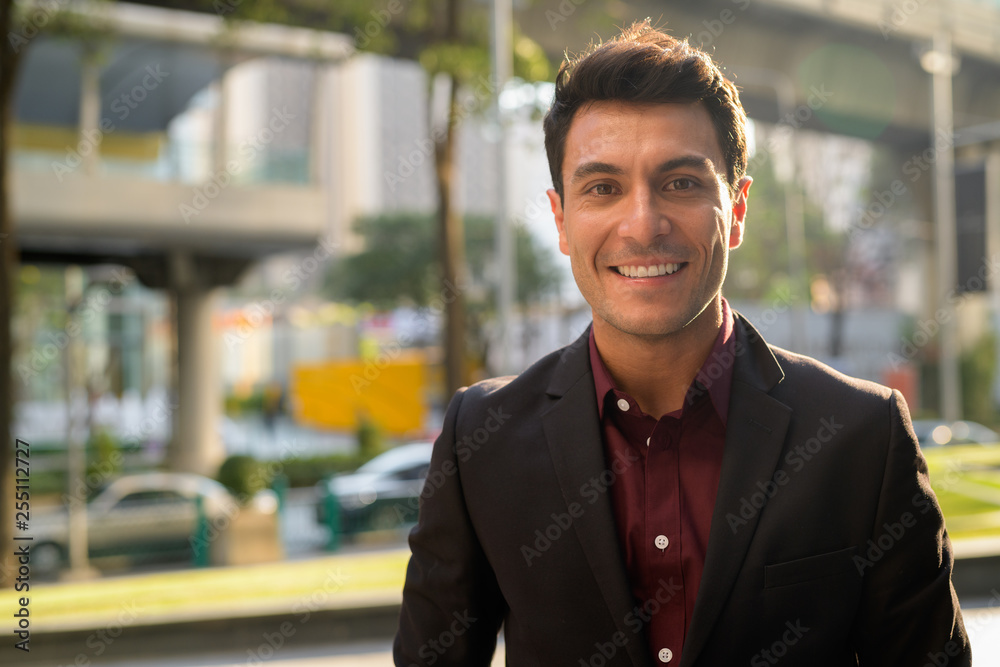 Fototapety, obrazy: Face of happy young handsome Hispanic businessman smiling in the city