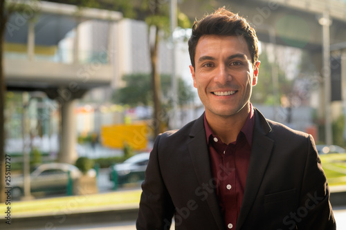 obraz PCV Face of happy young handsome Hispanic businessman smiling in the city