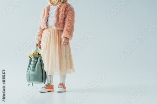 Fotografía  cropped view of cute kid holding bag with white tulips on grey background