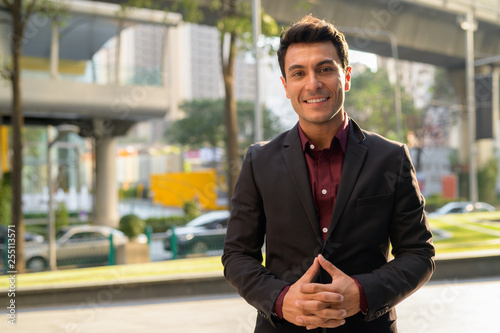 Fotografía  Young happy Hispanic businessman smiling in the city streets