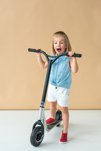 Smiling Kid In Shirt And Shorts Riding Scooter On Beige Background