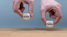"""True Or False? Two Hands Hold Two Dice With The Words """"TRUE"""" And """"FALSE"""". The Dice With The Label """"TRUE"""" Is Chosen."""