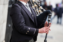 Scottish Bagpiper Dressed In Traditional Dress Performing On The Street
