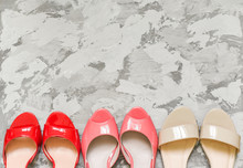 Beautiful Shoes And Sandals On A Gray Background, A Place For The Text. Flat Lay