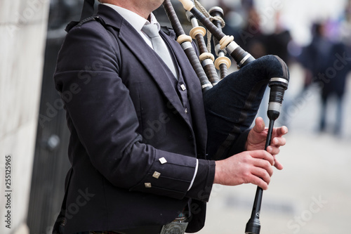 Tela Scottish bagpiper dressed in traditional dress performing on the street