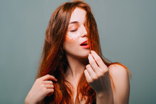 Young Fashion Model Portrait. Redhead Beauty. Woman With Auburn Hair. Closed Eyes. Glitter Freckles Makeup.