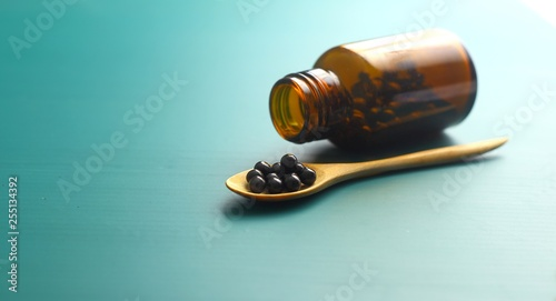 Black bolus on wooden spoon and bottle on green background Canvas Print