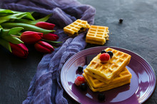 Traditional Belgian Waffles With  Berry Fruits On Dark Background, Homemade Healthy Breakfast.Red Tulips Background.
