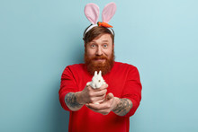 Funny Red Haired Man In Casual Clothes, Suggests To Buy Small Decorative White Bunny, Wears Long Rabbits Ears, Defends Rights Of Animals, Has Tattoos On Arms, Ready To Celebrate Easter Holiday