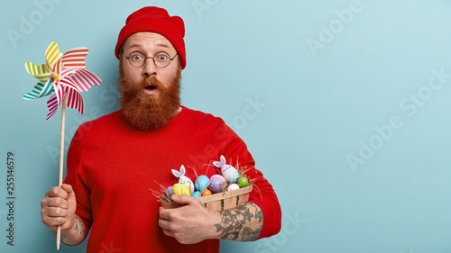 Photo sur Toile Pain Easter celebration concept. Stupefied man with foxy stubble, carries basket with dyed eggs on hay, holds paper windmill, shocked to find out religious rules during fixed feast, models indoor