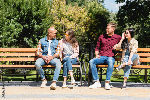 Fotografija cheerful multicultural friends sitting on benches in park