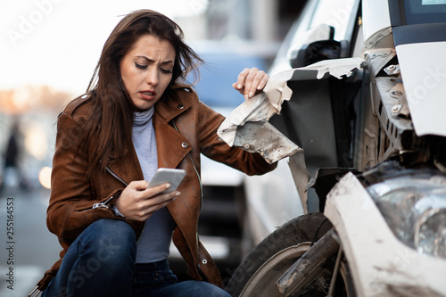 Young woman typing text message on mobile phone next to her wrecked car.