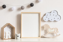 The Modern Scandinavian Newborn Baby Room With Mock Up Photo Frame, Wooden Toys And Children's Cup. Hanging Cotton Lamps And White Cloud. Minimalistic And Cozy Interior With White Walls. Real Photo.