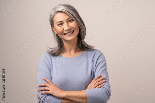 Foto  Smiling Asian senior woman with crossed arms