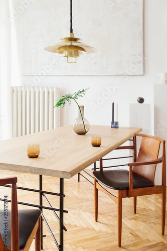 Stylish and modern dining room interior with design sharing table, chairs, gold pedant lamp, abstract paintings and elegant accessories Fototapet