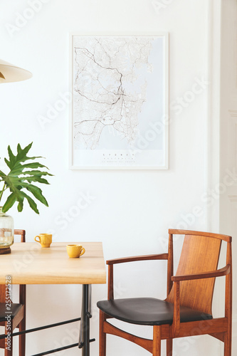 Stylish and modern dining room interior with mock up poster map, sharing table design chairs, gold pedant lamp and cups of coffee Wallpaper Mural
