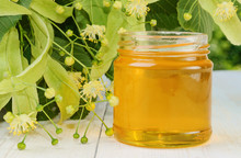 Jar Of Linden Honey And Flowering Linden On Wooden Table