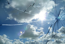 Large Cracks On The Texture Of A Broken Mirror, Glass Against A Blue Sky With White Clouds