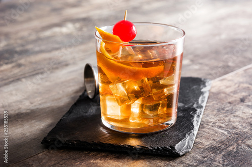 Old fashioned cocktail with orange and cherry on wooden table