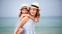 Happy Family At Beach. Mother And Child Daughter Hug At Sea.