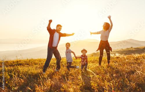 Fototapeta Happy family: mother, father, children son and daughter on sunset obraz na płótnie