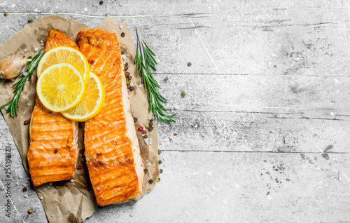 Foto Grilled salmon fillet with slices of fresh lemon.