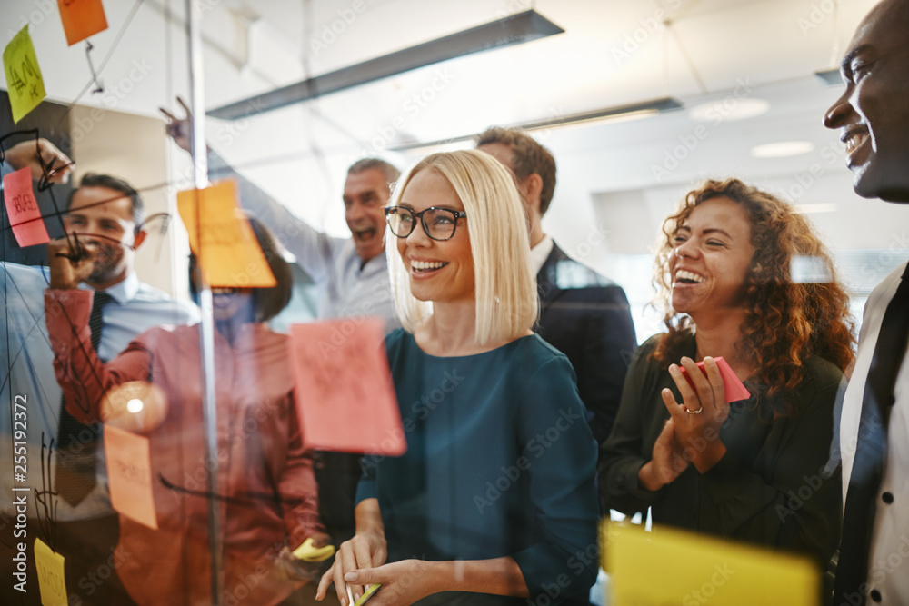 Fototapeta Diverse businesspeople brainstorming with notes on a glass wall