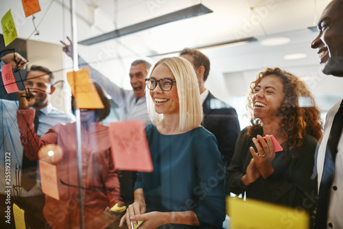 Obraz Diverse businesspeople brainstorming with notes on a glass wall - fototapety do salonu