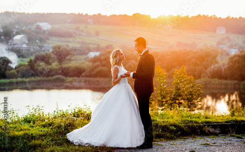 Fotografia  Lovely couple reach out their hands while standing in the rays sunny