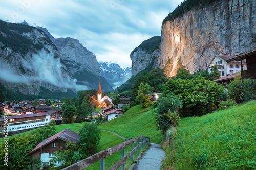 Obraz Amazing touristic alpine village with famous church and Staubbach waterfall, Lauterbrunnen, Switzerland, Europe - fototapety do salonu