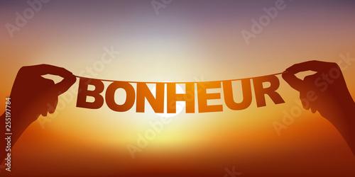 Valokuva  Concept du bien-être et de la joie de partir en vacances, avec deux mains qui tiennent une guirlande sur laquelle est écrit le mot bonheur devant un ciel ensoleillé