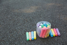 Plastic Transparent Box Full Of New Colorful Chalks Outdoors Isolated On Surface Of Grey Grunge Pavement As Background. Horizontal Color Photography.