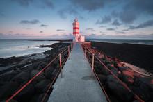 Old Lighthouse In Gardur, Keflavik, Iceland. Cloudy Sky And Choppy Sea. Beautiful Sunset Scene
